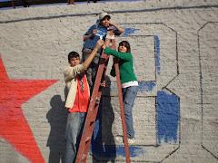 """Los pibes y las pibas """"del Maradona"""" pintando el mural"""