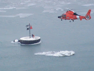 An MH-65 Dolphin helicopter crew from Air Station Detroit flies toward the Fighting Island Channel South Light on the Detroit River Jan. 3, 2011, to pick up two Coast Guardsmen who were dropped off earlier in the day to perform maintenance on the aid to navigation. U.S. Coast Guard photo.