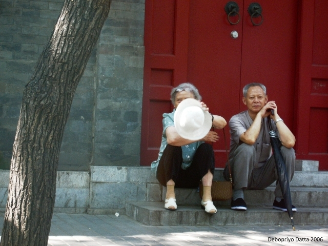 An afternoon meeting . . .perhaps Interestingly, the lady was trying to shield her face from the camera. The man looked on unperturbed. Shot from a taxi. Beijing, September 2006