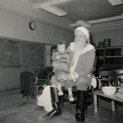 My dad playing Santa- me on his lap