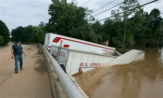 An unidentified man looks back at tractor trailer cars washed against a bridge going over Sweetwater Creek left there by flood waters from recent rains, Wednesday, Sept. 23, 2009, in Austell, Ga.(AP Photo/John Amis)