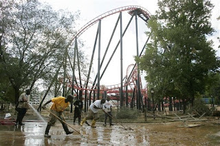 Grounds crew including Michael Watts, Jr., second from left, work at cleaning up mud and debris at the foot of the Ninja roller coaster, left by flood waters that inundated Six Flags over Georgia amusement park, Thursday, Sept. 24, 2009, in Atlanta. (AP Photo/John Amis)