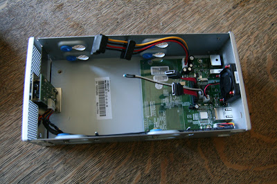 A great look inside the NAS device.  A board, a fan, a heat sensor, a power supply and some cables.