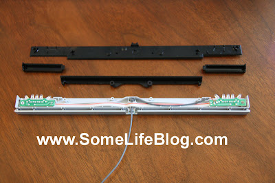 Now remove the center black plastic piece from the sensor bar. This is a simple lifting of the piece that is held in place by the two round pieces in the center that it sets on. Simply lift it straight up to remove from the sensor bar.