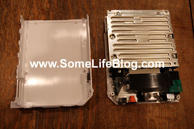 Set the cover to the side to expose the internals of the Nintendo Wii including the DVD-ROM cover.