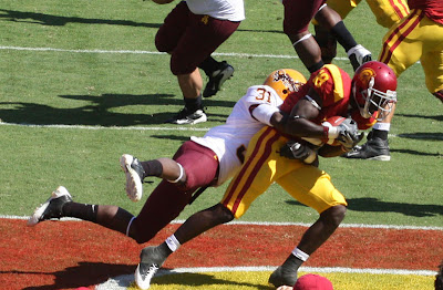 Damian Williams #18 catches Mark Sanchez's pass for a touchdown while being closely defended by an Arizona State player.