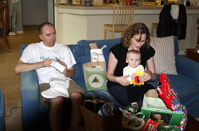 Dominic and Kimberly open gifts as their 7-month old, Lincoln watches.