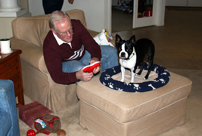 My dad opens Sadie's (Boston Terrier) stocking and hands her a gift.