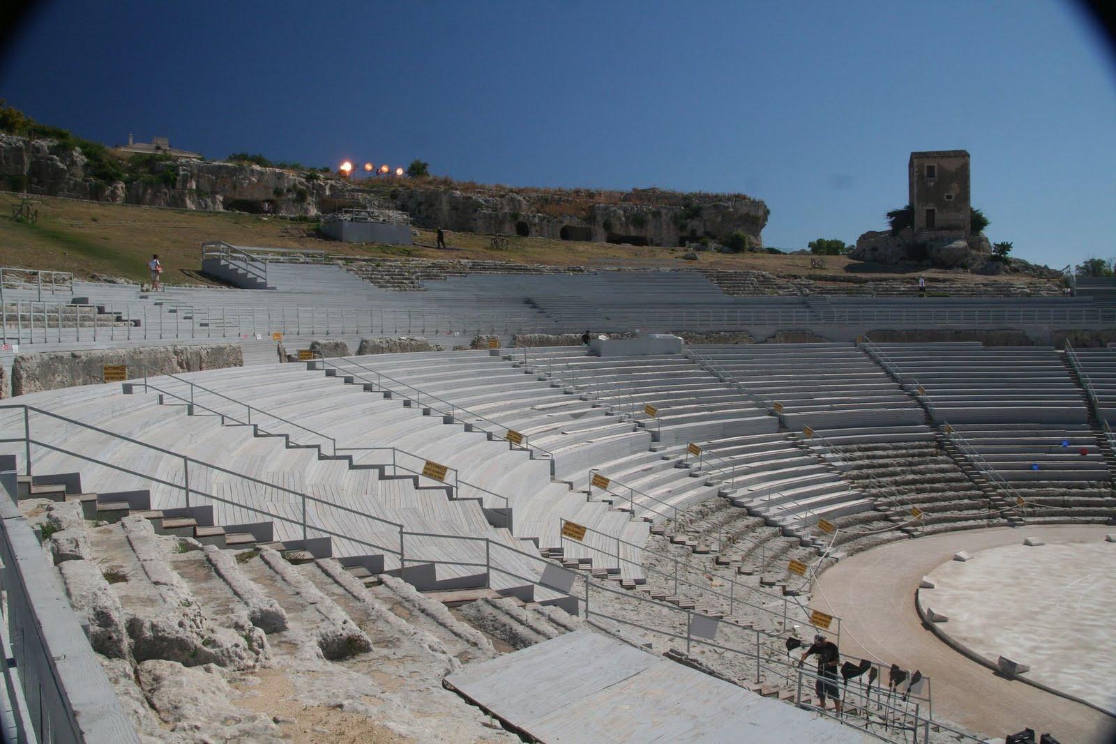 el teatro se alza en una zona carente de vegetacion en la parte superior hay paredes rocosas con muchas cavidades votivas asi como una pequena gruta