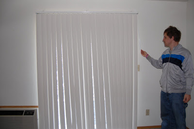 Zach adjusting the blinds in his new apartment