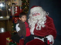 Toddler boy sitting on Santa Clause's lap