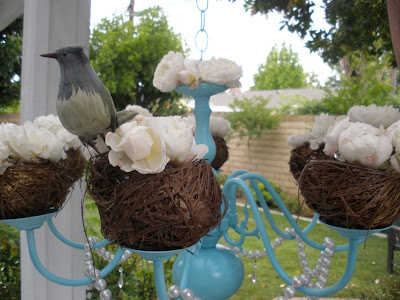 Roses and bird nests on a turquoise chandelier.