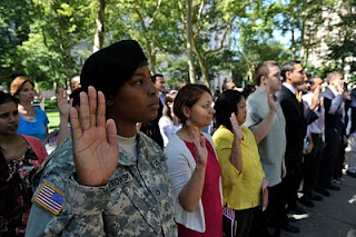 Army PFC Lafiette Trowers joins her fellow new citizens in taking the Oath of Allegiance