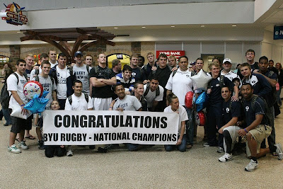 The BYU Rugby team enjoys a moment of celebration with fans upon arrival at the Salt Lake airport