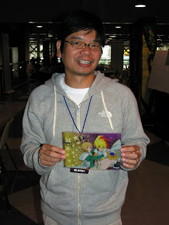 Masahiko Minami, president of BONES animation studio, holding up a promotional image from Star Driver