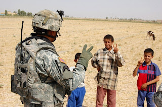 "Shared Hope Sgt. 1st Class Ernest Oberst, Gladstone, Mich., native, teaches Iraqi children how to make the peace sign during Operation Hammer Bonzai XI in the Taji Qada, northwest of Baghdad. Oberst serves as an infantry platoon sergeant in Company B, 52nd Infantry Regiment, 1st Battalion, 27th Infantry Regiment ""Wolfhounds,â€‌ 2nd Stryker Brigade Combat Team ""Warrior,â€‌ 25th Infantry Division, Multi-National Division – Baghdad. Photo by Staff Sgt. J.B. Jaso."