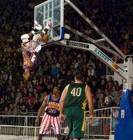 A Harlem Globetrotter does a slam-dunk