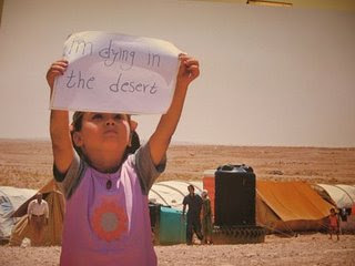 A Palestinian Iraqi child holds up a sign saying 'I'm dying in the desert' in the Al-Tanf refugee camp.