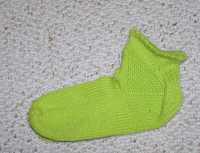a green ankle sock with a garter-stitch triangle gusset