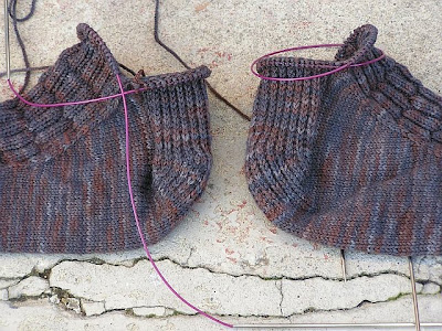 two unfinished socks, back to back, focused on the heels and increase section