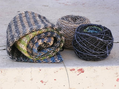 a striped scarf in progress, rolled up, sitting beside two cakes of yarn