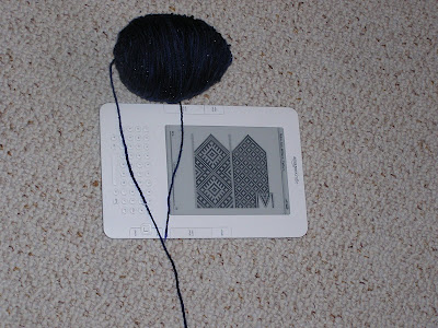 a ball of yarn beside a kindle showing a mitten-knitting chart