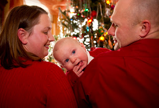 Minneapolis parents hold lovely baby girl by a Christmas tree
