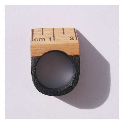 Ebonised oak ring with a section of wooden ruler set at an angle.