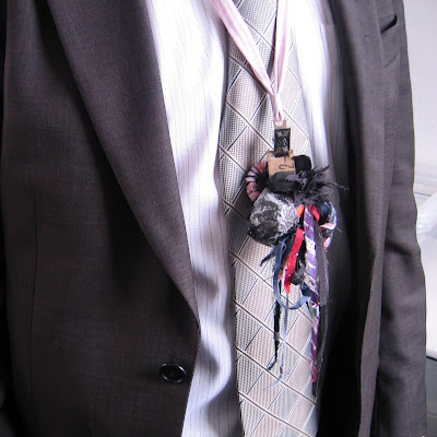 Man in suit wearing a hand-made lanyard assemblage constructed out of office based materials and strips of suits and shirts.