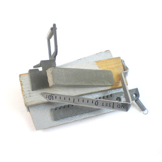 Office assemblage pin, includes concrete, typewriter parts and wood.