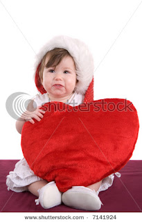 baby wishing happy valentines day with a heart