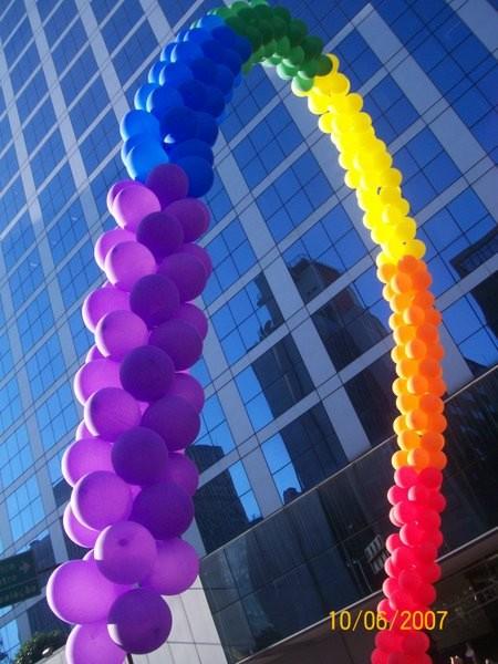 Um arco-íris de borracha e hélio sobre um prédio de vidro
