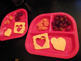 slices on cheese on a lunch tray cut out with a heart-shaped cookie cutter