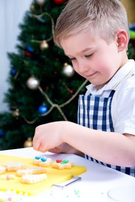 NAMC montessori activities meaningful winter celebrations scholastic boy decorating cookies
