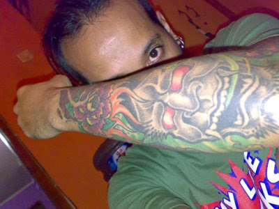 Bone tattoo in blood red background on right forearm. Devil tattoo on left