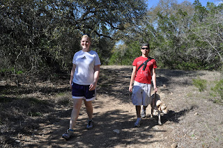 Front view of Darrell and Egypt and Shelly walking towards me on the path, theres trees behind and shade covering about half the trail.