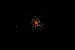 this firework is smaller and you can see its trail also, it is mainly orange with purple outbursts from the center