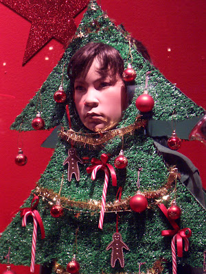 A sad dummy dressed like a Christmas tree