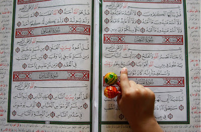 http://1.bp.blogspot.com/_58eOM8Ne2EA/TFeizH37E8I/AAAAAAAAAOM/1ZplosWK1uk/s1600/Reading+the+Quran--child+with+lollipops+Boston.com