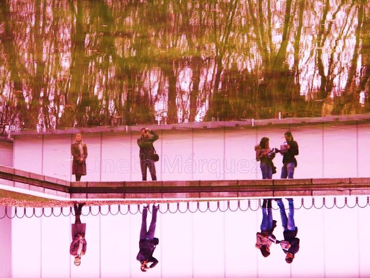 Turistas reflejados en lago de Plaza España