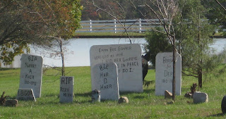 Fake tombstones with inscriptions like R.I.P Narry A. Kair, and I.B. Gott, and R.I.P. Har D. Harr, and Emma B. Goner