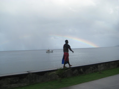 An Islander walking on a concrete wall next to the ocean with a rainbow above his head