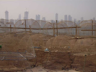 Fishing traps dry in the sun with the Doha skyline in the distance