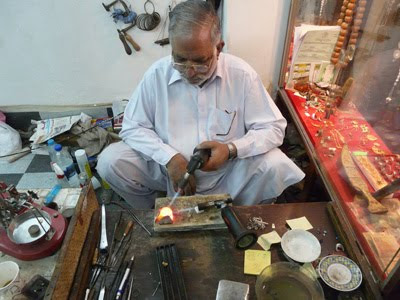 Hot flames burn as this jewelry maker focuses on a silver ring.