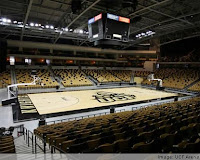 Empty UCF basketball arena with gold and black seats and basketball court with black border.