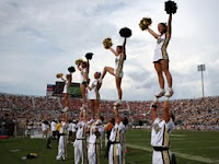 Series of five female UCF cheerleaders standing on the hands of five male cheerleaders that are hoisting the white uniformed girls on the sideline of a football game.