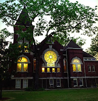 Victorian dark brick building with illuminating yellow light windows at dusk.  A large tree with expansive leafy branches sits in the foreground.
