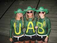 Three girls in black shirt wear green cowboy hats and paint yellow letters on their green painted chests and wife beater shirts spelling UAB.