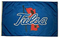Dark blue flag with light blue cursive spelling of Tulsa over a red waiving flag.