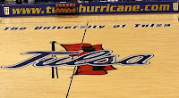 Close up view of center court of a basketball court with blue cursive writing spelling Tulsa painted on the floor over the painting of a red flag blowing on a black flag pole.  Above the painting are the words The University of Tulsa written in blue.